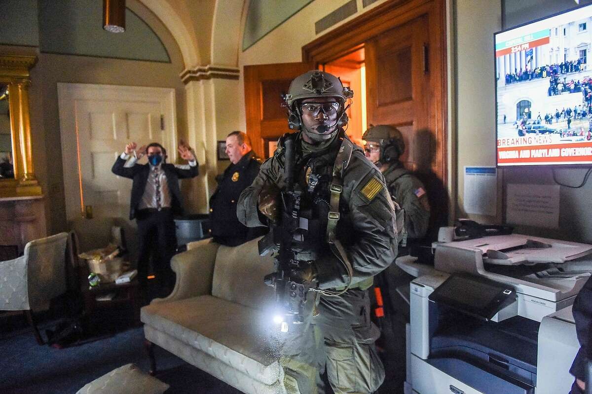 A Congress staffer holds his hands up while Capitol Police Swat team check everyone in the room as they secure the floor of Trump supporters in Washington, DC on January 6, 2021.