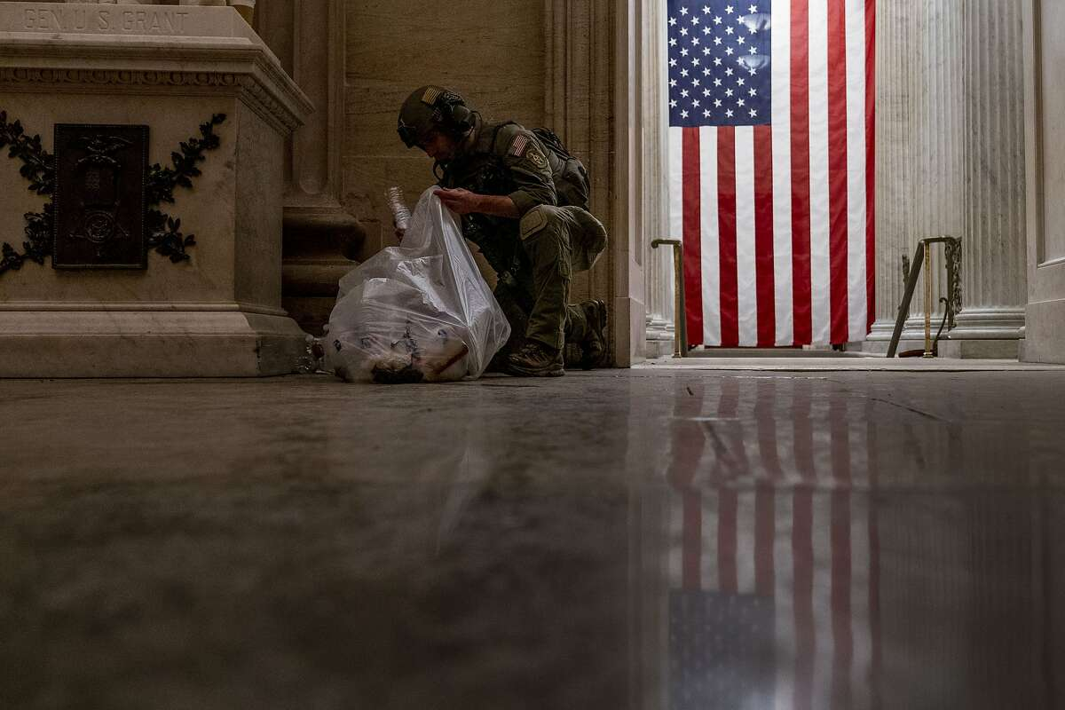 An ATF police officer cleans up debris and personal belongings strewn across the floor of the Rotunda in the early morning hours of Thursday, Jan. 7, 2021, after Trump supporters stormed the Capitol in Washington, on Wednesday.