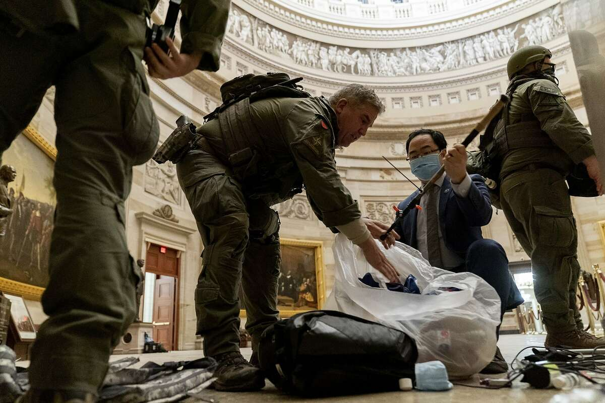 Rep. Andy Kim, D-N.J., helps ATF police officers clean up debris and personal belongings strewn across the floor of the Rotunda in the early morning hours of Thursday, Jan. 7, 2021, after Trump supporters stormed the Capitol in Washington, on Wednesday.