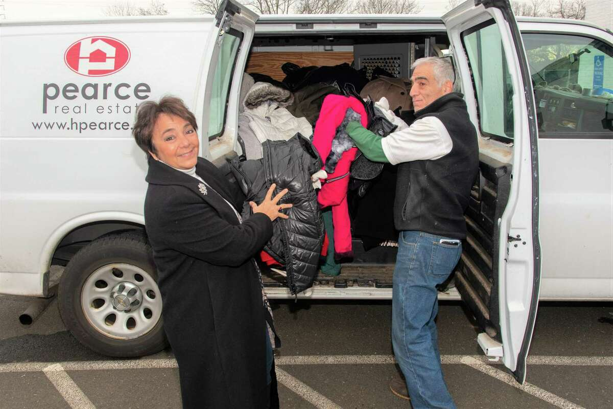 Pearce Real Estate President Nanette Pastore, left, and Gene Cufone, facilities manager for Pearce, with some of the items donated in Pearce's coat drive.