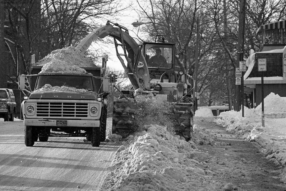 """From the front page of the News Advocate on this day in 1981, """"In case you were wondering what happens to those decorative 1980 Christmas trees when all the festivities die down, this photo tells the story. A city employee feeds one of the evergreens into the chipper this morning on Fifth Street.""""(Manistee County Historical Museum photo)"""
