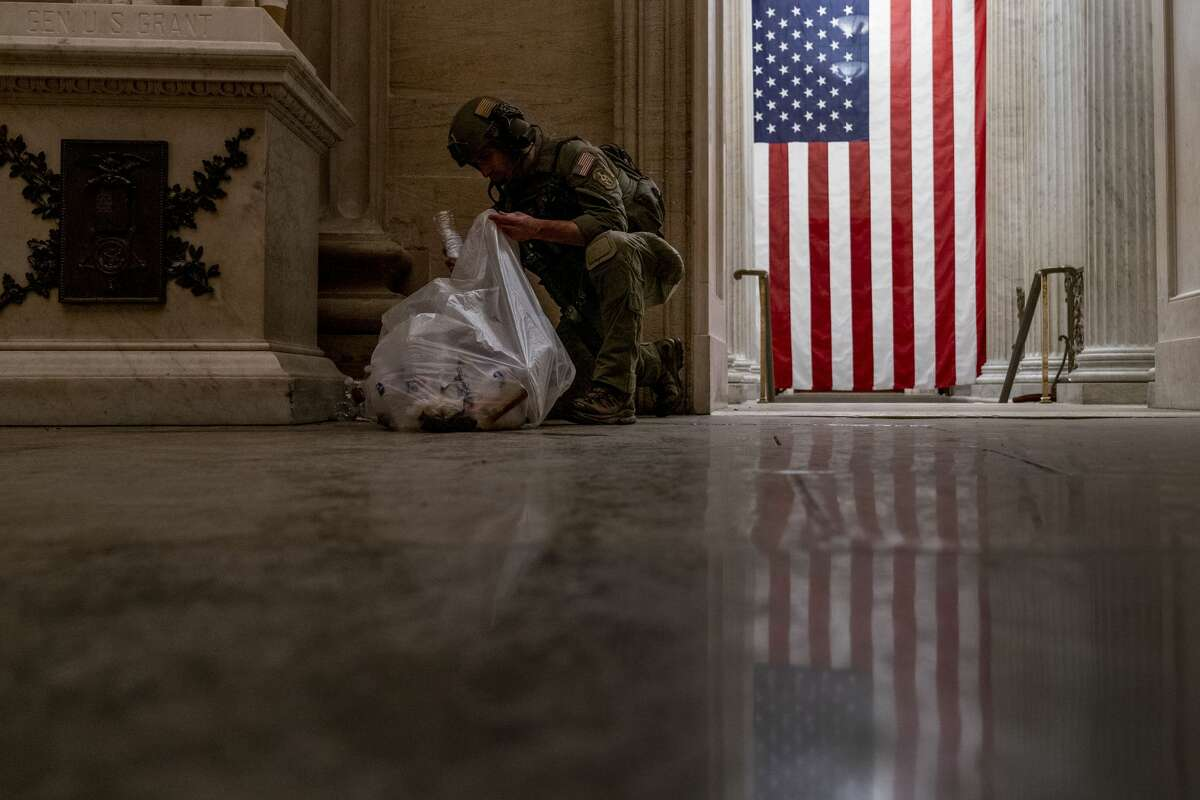 An ATF police officer cleans up debris and personal belongings strewn across the floor of the Rotunda in the early morning hours of Thursday, Jan. 7, 2021, after protesters stormed the Capitol in Washington, on Wednesday. (AP Photo/Andrew Harnik)