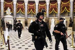 Members of the Swat team patrol and secure the Statuary Hall before US Vice President makes his way into the House Chamber, at the US Capitol, on January 7, 2021 in Washington, DC. - Congress was on track on January 7, 2021 to certify Joe Biden as the next US president and deal a hammer blow to Donald Trump whose supporters stormed the Capitol hours earlier, triggering unprecedented chaos and violence in the seat of American democracy. (Photo by Olivier DOULIERY / AFP) (Photo by OLIVIER DOULIERY/AFP via Getty Images)