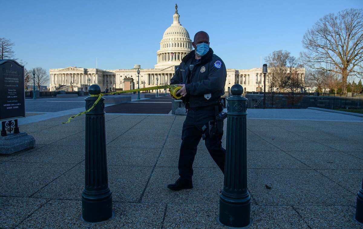 FILE. Letter writer says 'abject failure' of Capitol Police must be investigated by Congress. Here, a Capitol Police officer tapes off access in Washington, DC, on January 7, 2021, one day after supporters of outgoing President Donald Trump stormed the building. (NICHOLAS KAMM/AFP via Getty Images)