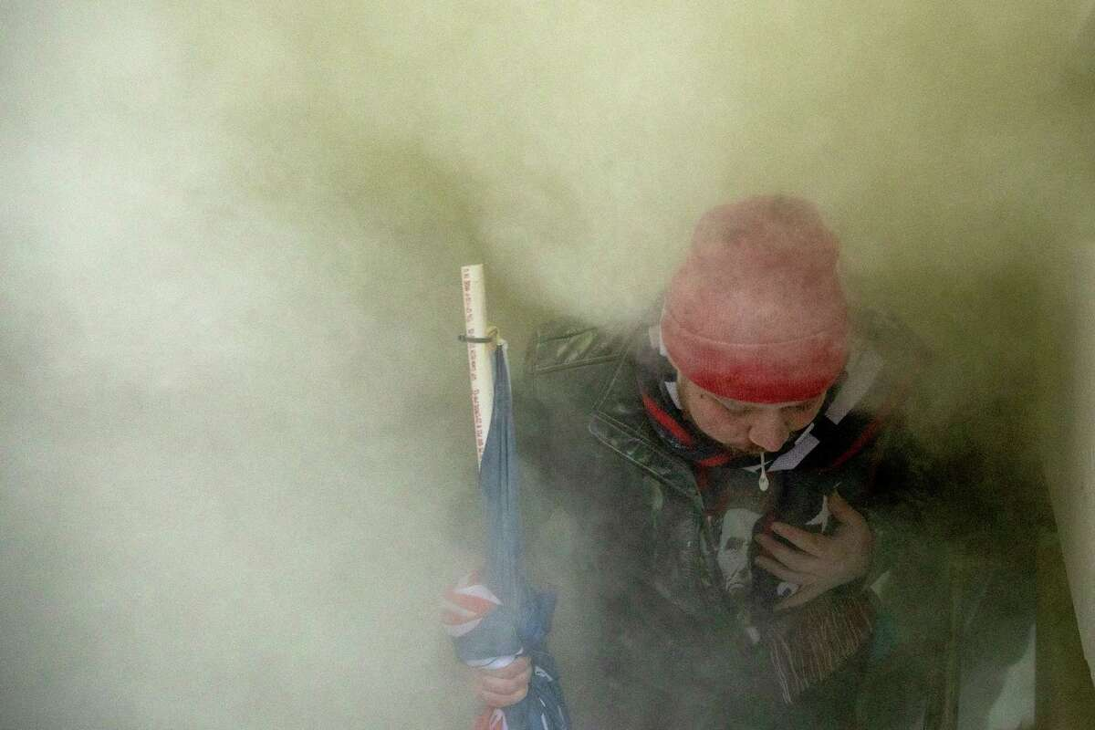 A Trump supporter spits out a chemical irritant that was sprayed out of a door of the U.S. Capitol.