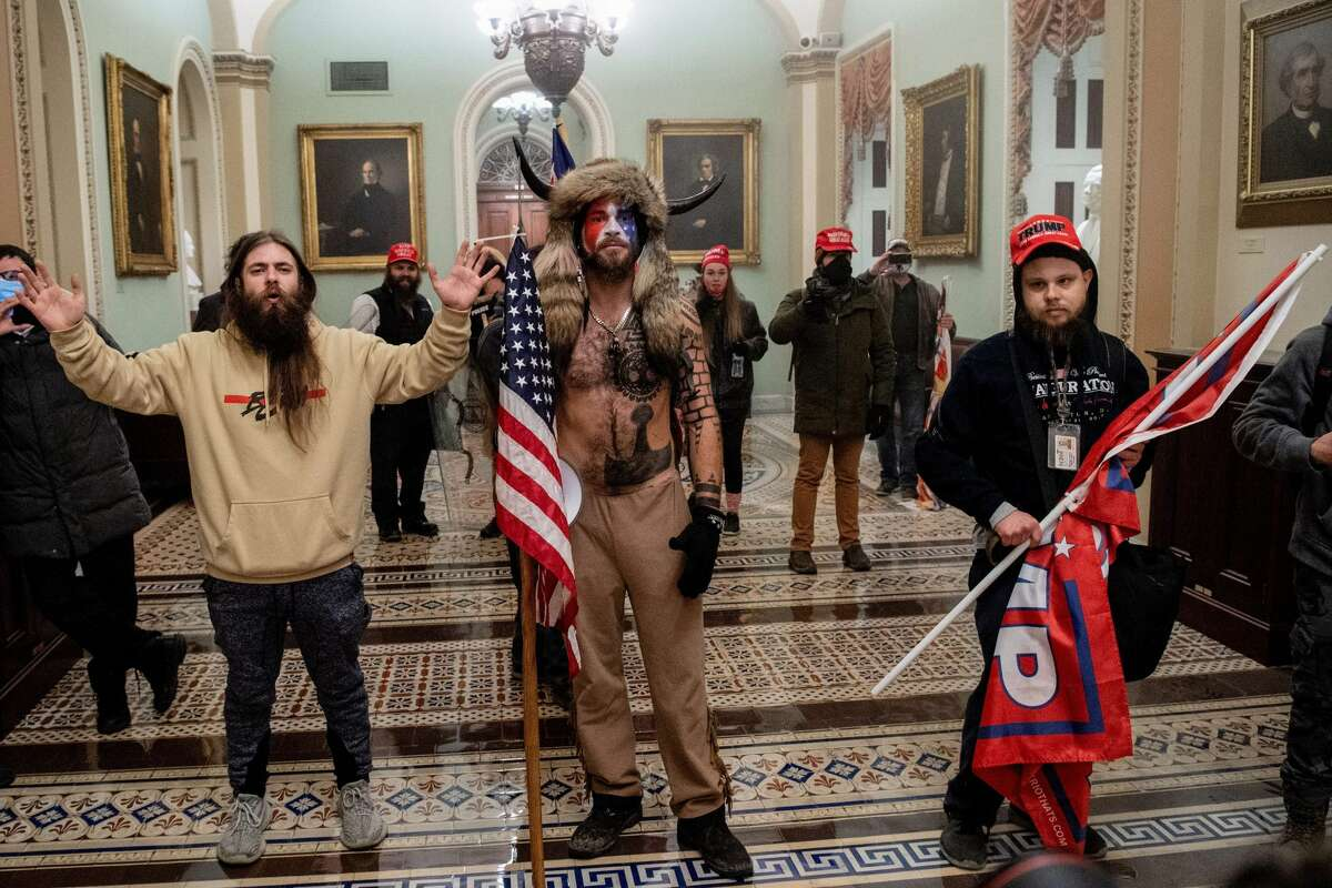 Supporters of US President Donald Trump, including Jake Angeli, a QAnon supporter known for his painted face and horned hat storms through US Capitol halls.