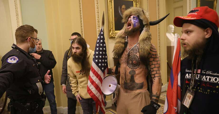 Jake Angeli, who calls himself the Q Shaman, seen inside the Capitol building on Wednesday. Photo: Win McNamee, TNS