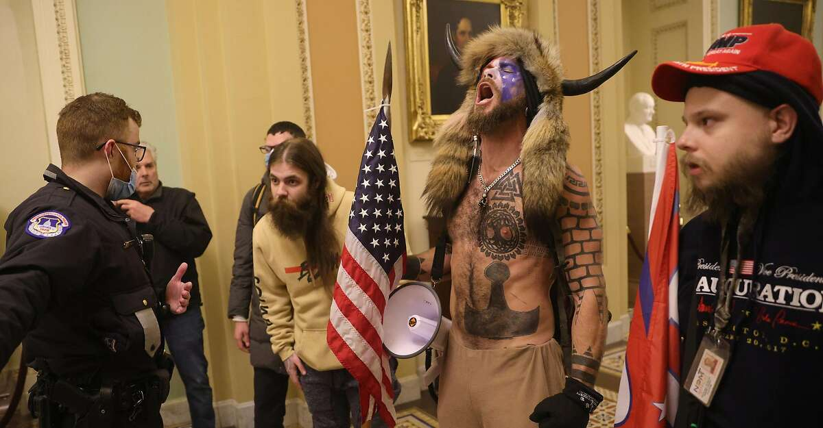 Jake Angeli, who calls himself the Q Shaman, seen inside the Capitol building on Wednesday.