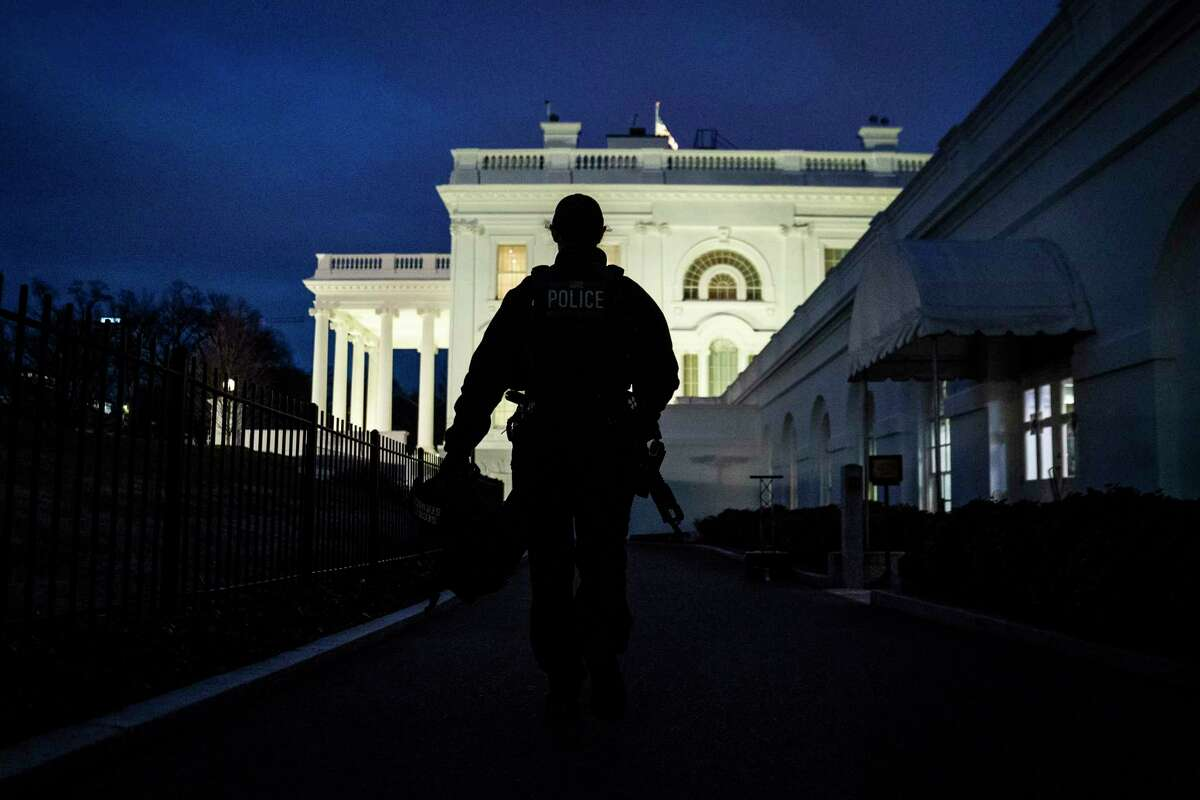 An armed police officer walks toward the White House on Wednesday evening.