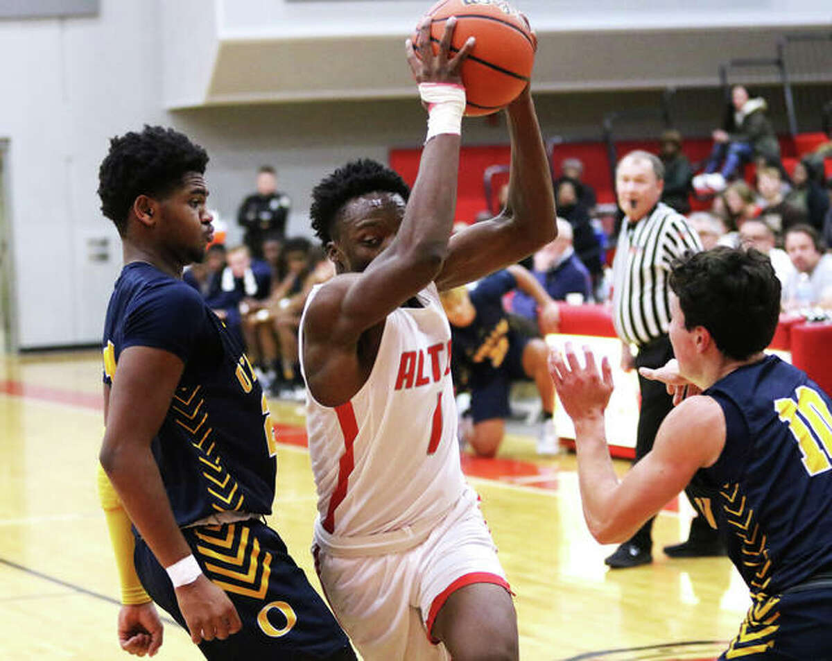 Alton's Ja'marcus Gary (middle) splits O'Fallon defenders on his drive to the basket during a SWC game last season at Alton High in Godfrey. Gary, now a senior, and his Redbird teammates are still waiting for a decision on the 2020-21 basketball season.