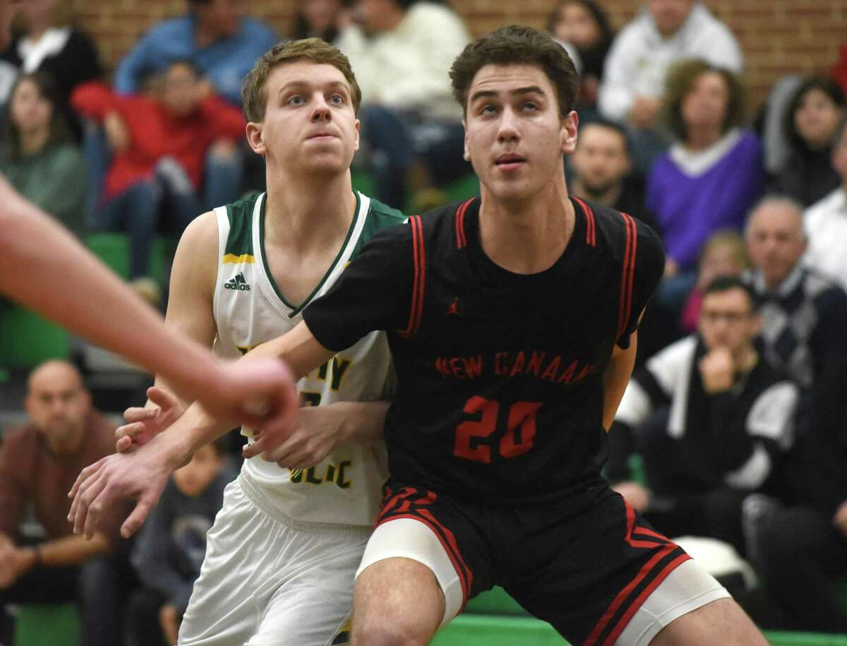 New Canaan's Leo Magnus (20) and Trinity's Matthew Dougherty (20) battle for position on a free throw during a boys basketball game at Trinity Catholic High School in Stamford on Friday.