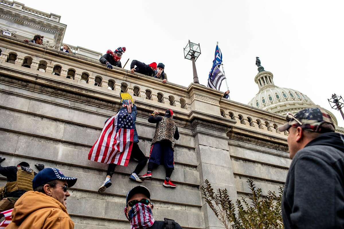 Supporters of President Donald Trump scale a wall on the Senate side of the Capitol Building in an attempt to disrupt the certification of the Electoral College results, Jan. 6, 2021. The mob in Washington attempting to disrupt the peaceful transition of American power also posed a threat to all democracies.