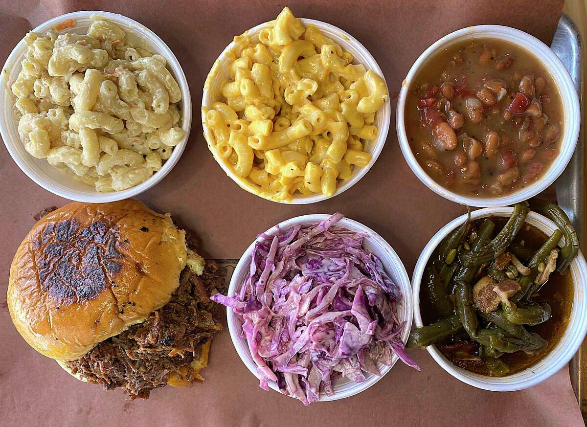 The menu at Bandit BBQ at Freight Gallery & Studios includes, clockwise from bottom left, a chopped barbecue sandwich, Hawaiian macaroni salad, mac and cheese, pinto beans, green beans and cole slaw.