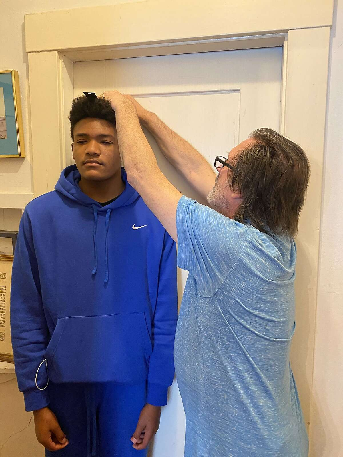 Zane Fisher-Paulson gets his height measured by his father, Brian, during the family's annual Talling of the Boys.