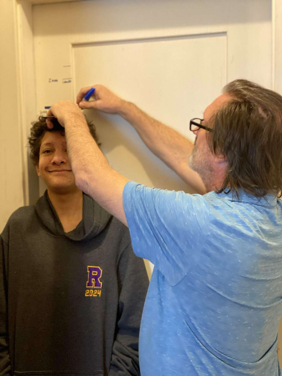 Aidan Fisher-Paulson gets his height measured by his father, Brian, during the family's annual Talling of the Boys on January 1, 2021.