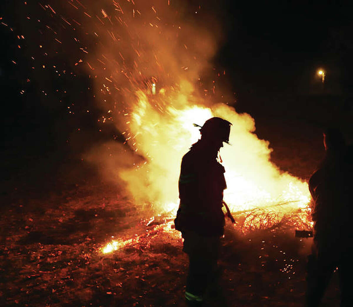 An Alton firefighter walks past a pile of burning Christmas trees Wednesday night in the Cousley Sunken Gardens adjacent to Riverview Park. The tree burning was a Twelfth Night tradition and about 50 neighborhood residents turned out to watch. Residents at the sunken garden maintained social distancing for the event.