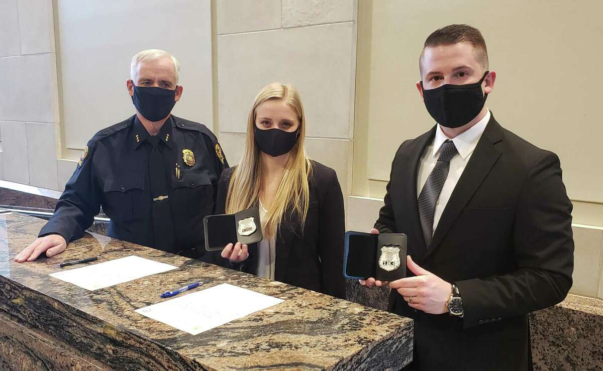 Police Chief James Heavey, left, gives badges to two new recruits, Kassidy Schupp, center, and James Ketterer, right, at police headquarters this week.