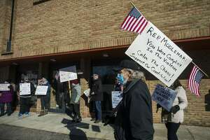 A group of people gather Thursday, Jan. 7, 2021 outside of U.S. Rep. John Moolenaar's Midland office to protest his support of President Donald Trump, one day after a mob of Trump supporters breached the U.S. Capitol in Washington, D.C. (Katy Kildee/kkildee@mdn.net)