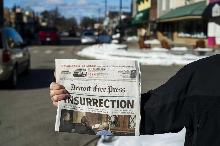 Michael Clift holds up an edition of the Detroit Free Press as a group of people gather Thursday, Jan. 7, 2021 in downtown Midland to protest U.S. Rep. John Moolenaar's support of President Donald Trump, one day after a mob of Trump supporters breached the U.S. Capitol in Washington, D.C. (Katy Kildee/kkildee@mdn.net) Photo: (Katy Kildee/kkildee@mdn.net)