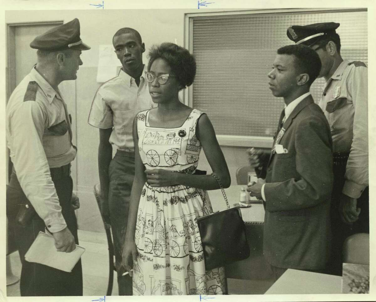 In this file photo from July 21, 1961, an unidentified Houston police officer and others are shown with Eldrewey Stearns, right, head of the Progressive Youth Association. They were in custody at the Houston police station after being arrested by HPD at the Union Station coffee shop in Houston to end a sit-in demonstration.