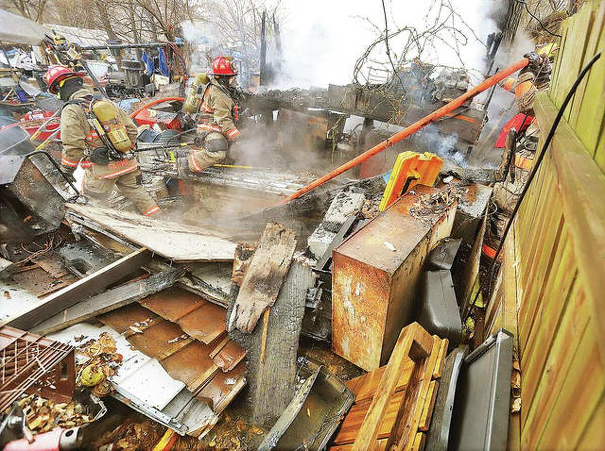 Firefighters stuggle for balance as they work around obstacles that cluttered a yard on Watt Lane off Wenzel Road in Godfrey Thursday where a structure was burning. No injuries were reported, but a Madison County deputy was sent to the scene when a resident of the property began yelling at firefighters as they attempted to put out the fire.