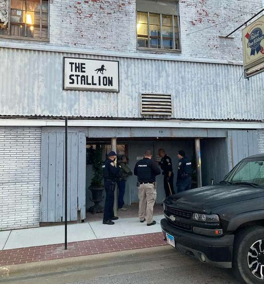 Law enforcement officers stand outside The Stallion Bar in Wood River on Dec. 23. Officials last month deemed the building uninhabitable. On Thursday, the city revoked the bar's liquor license.