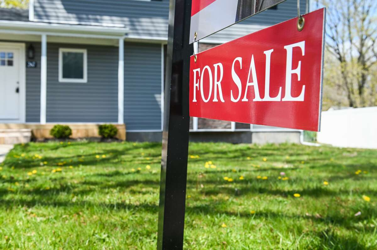"""A """"for sale"""" sign in front of a home in Wyandanch, New York, on April 22, 2020."""