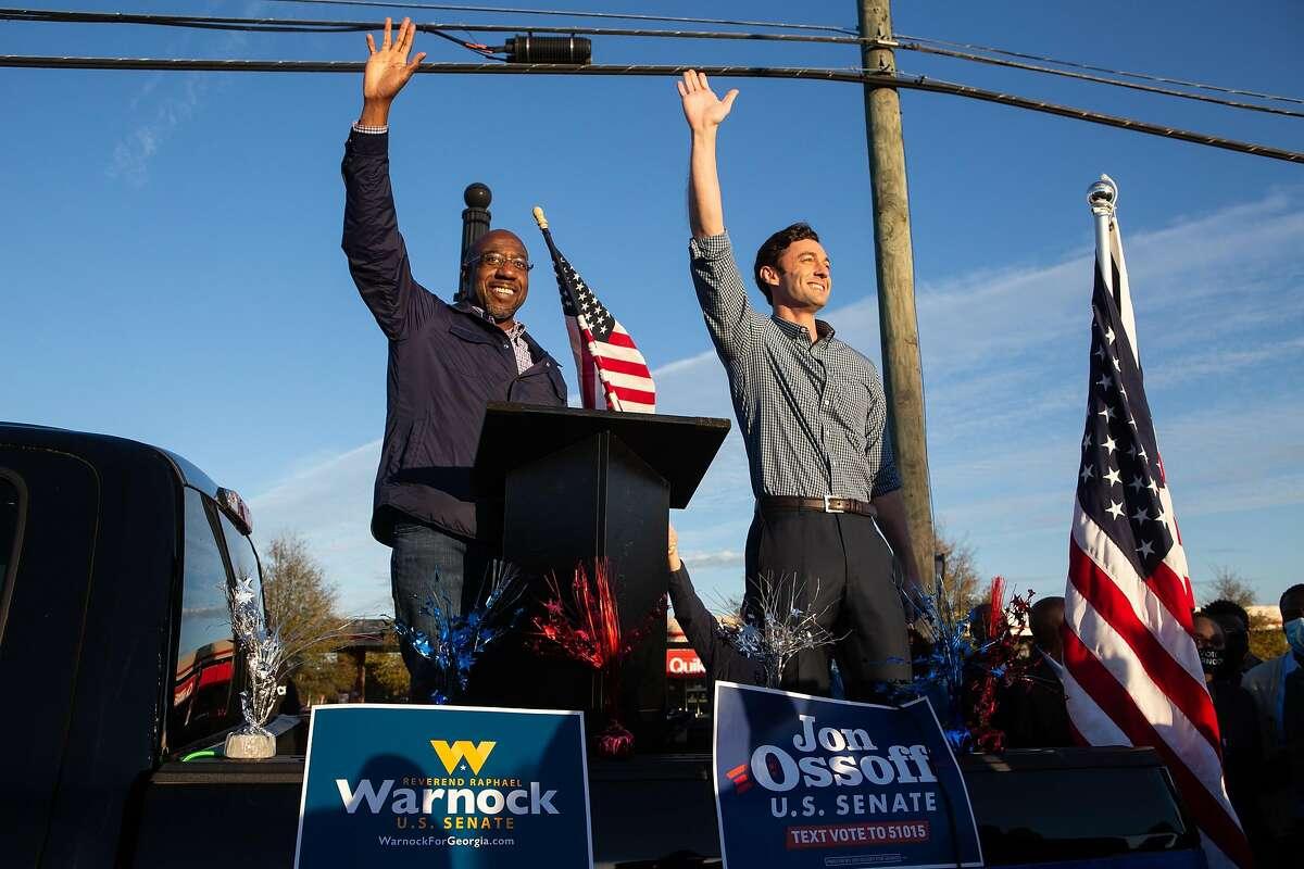 Democratic U.S. Senate candidates Jon Ossoff, right, and Raphael Warnock of Georgia wave to supporters during a rally on Nov. 15 in Marietta, Ga.