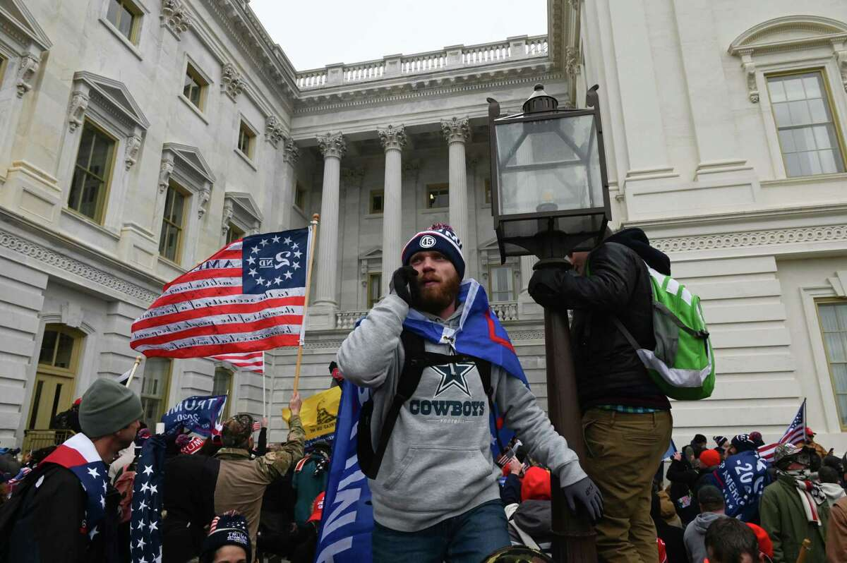 """Supporters of US President Donald Trump protest as they storm the US Capitol on January 6, 2021, in Washington, DC. - Demonstrators breeched security and entered the Capitol as Congress debated the a 2020 presidential election Electoral Vote Certification. President-elect Joe Biden denounced the storming of the US Capitol as an """"insurrection"""" and demanded President Donald Trump go on television to call an end to the violent """"siege."""" (Photo by ROBERTO SCHMIDT / AFP) (Photo by ROBERTO SCHMIDT/AFP via Getty Images)"""