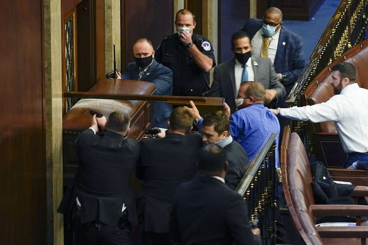 U.S. Capitol Police with guns drawn stand near a barricaded door as protesters try to break into the House Chamber at the Capitol on Wednesday.