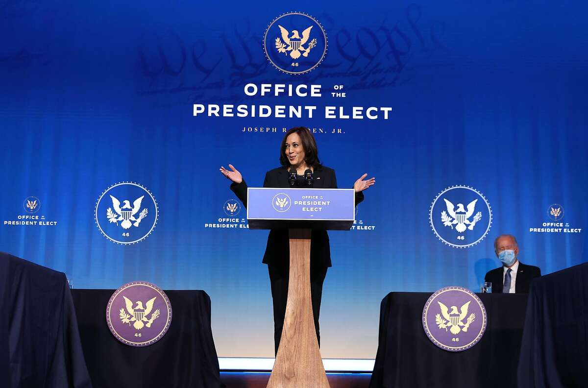 U.S. Vice President-elect Kamala Harris delivers remarks as President-elect Joe Biden looks on at The Queen theater Jan. 7, 2021, in Wilmington, Del.