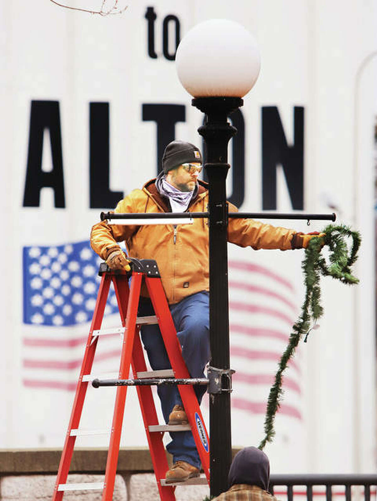 Matt Sowders, an employee of the Alton Parks and Recreation Departmet, removes the last of the Christmas garland from Lincoln-Douglas Square in downtown Alton Thursday.
