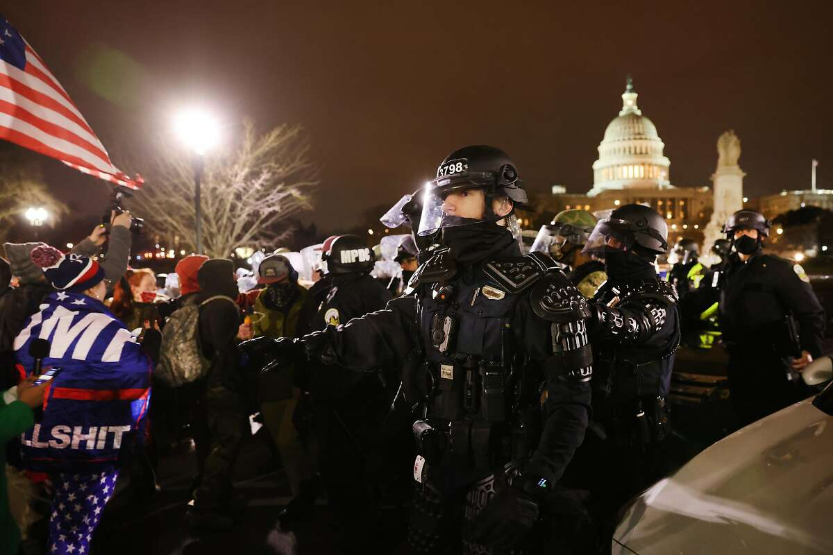 """WASHINGTON, DC - JANUARY 06: Members of the National Guard and the Washington D.C. police keep a small group of demonstrators away from the Capital after thousands of Donald Trump supporters stormed the United States Capitol building following a """"Stop the Steal"""" rally on January 06, 2021 in Washington, DC. The protesters stormed the historic building, breaking windows and clashing with police. Trump supporters had gathered in the nation's capital today to protest the ratification of President-elect Joe Biden's Electoral College victory over President Trump in the 2020 election. (Photo by Spencer Platt/Getty Images)"""