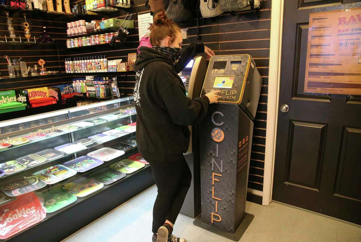 Bridgette McFarlin of Smokerz Paradise on Pat Booker Road demonstrates how to conduct a transaction on a Bitcoin ATM.