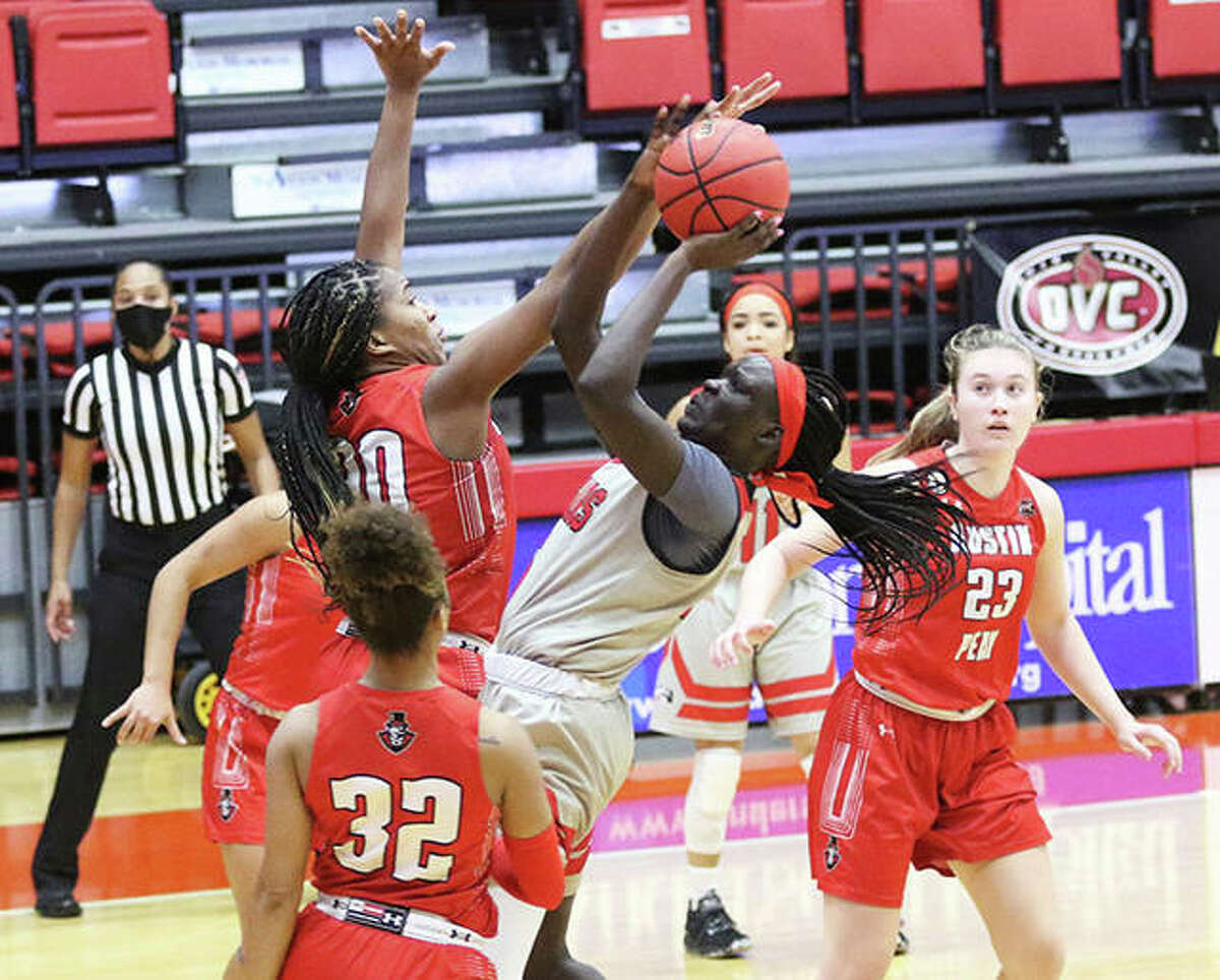 SIUE's Ajulu Thatha (middle) shoots in the lane and draws a foul from Austin Peay's Kemia Ward (30) in the first half Thursday afternoon at First Community Arena in Edwardsville.