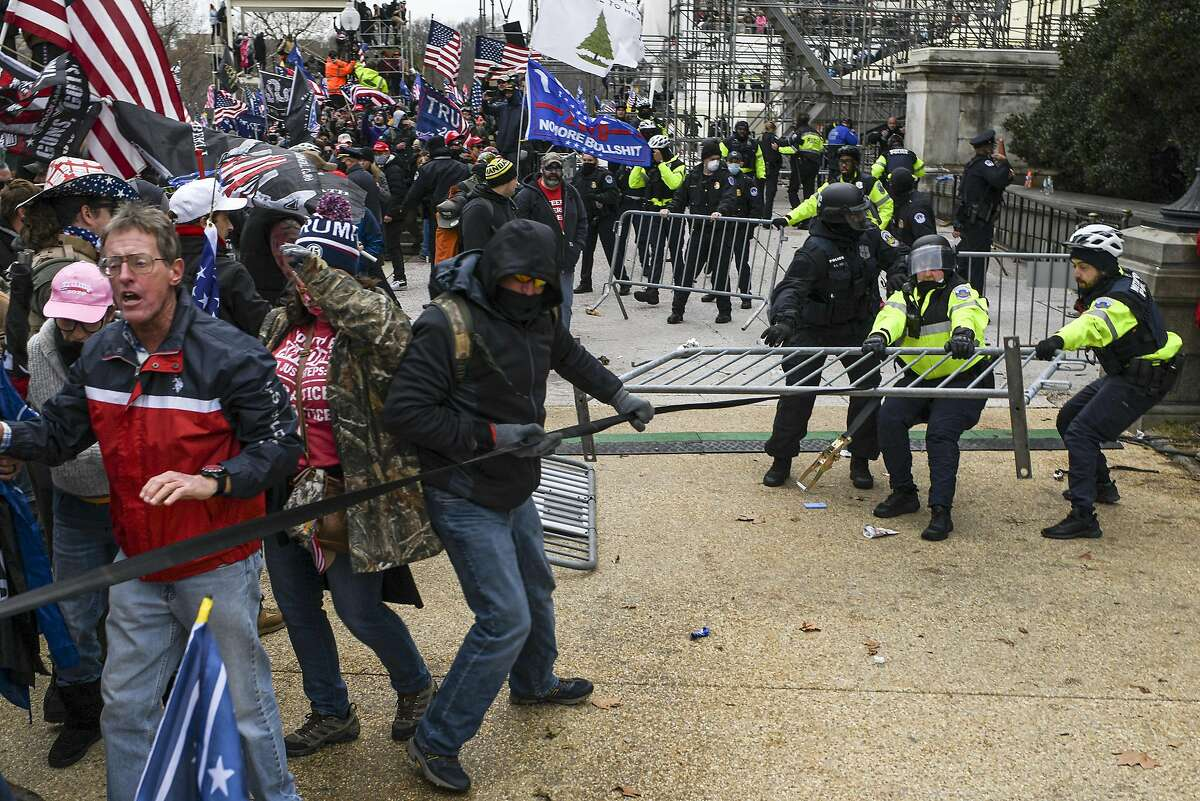 Protesters struggle with police for a security barricade at the Capitol in Washington, Wednesday, Jan 6.