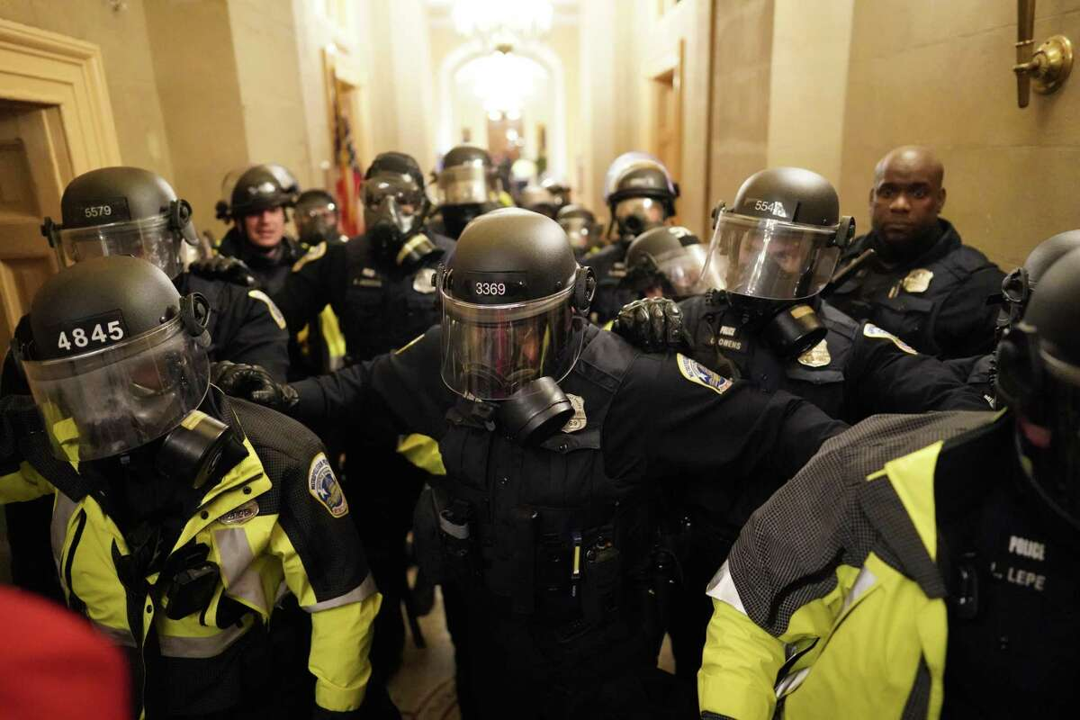 Riot police clear the hallway inside the Capitol on Wednesday, Jan. 6, 2021 in Washington, D.C.