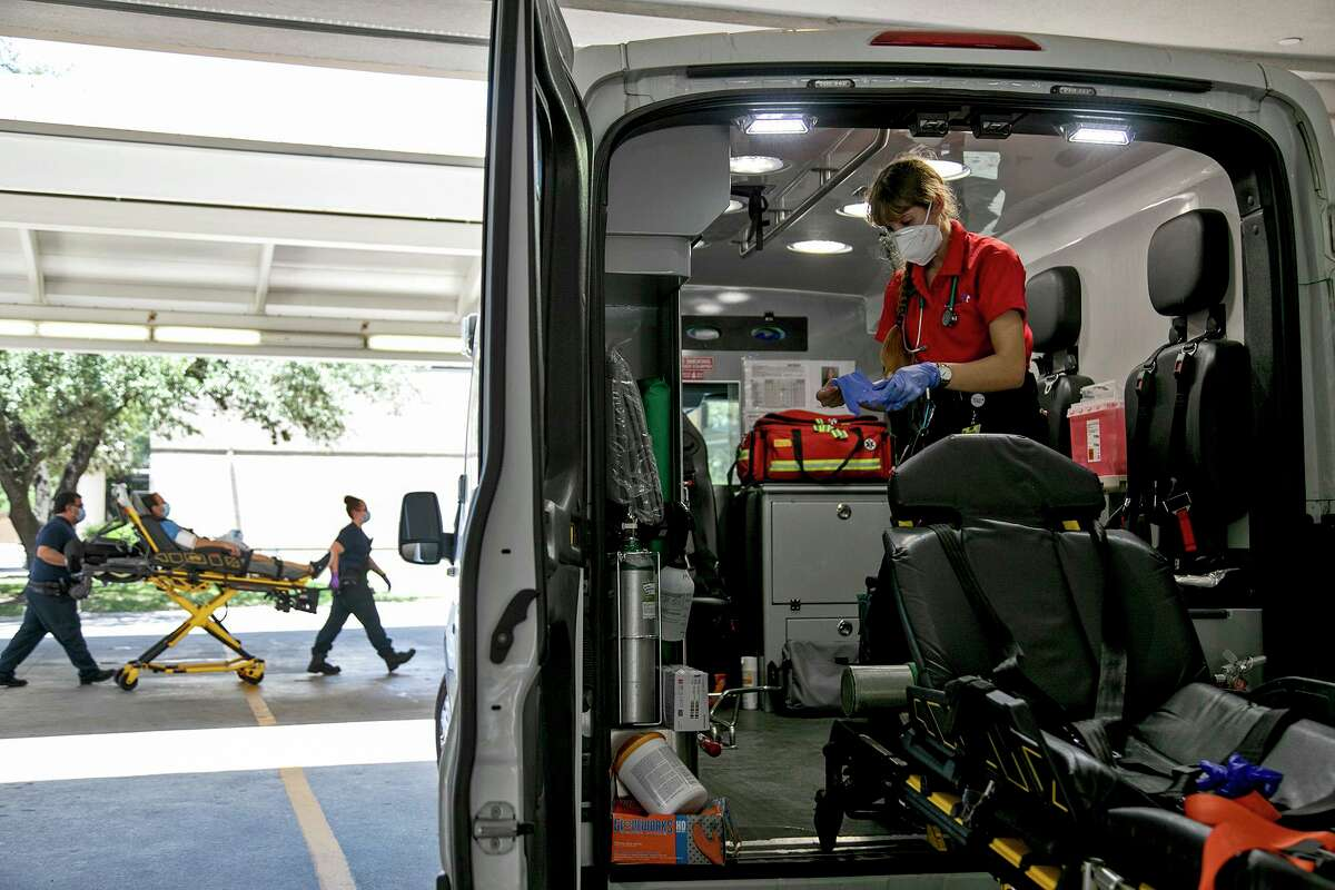 Paramedic Katheryn Wieding cleans the Superior Mobile Health ambulance after transferring a patient to a hospital on July 14 in San Antonio.