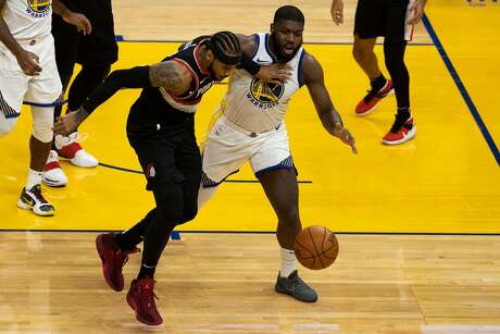 Golden State Warriors forward Eric Paschall (7) and Portland Trailblazers forward Carmelo Anthony (00) fight for a loose ball during the fourth quarter of a NBA basketball game on Friday, Jan. 1, 2021 in San Francisco, Calif.. The Trailblazers defeated the Warriors 123-98.