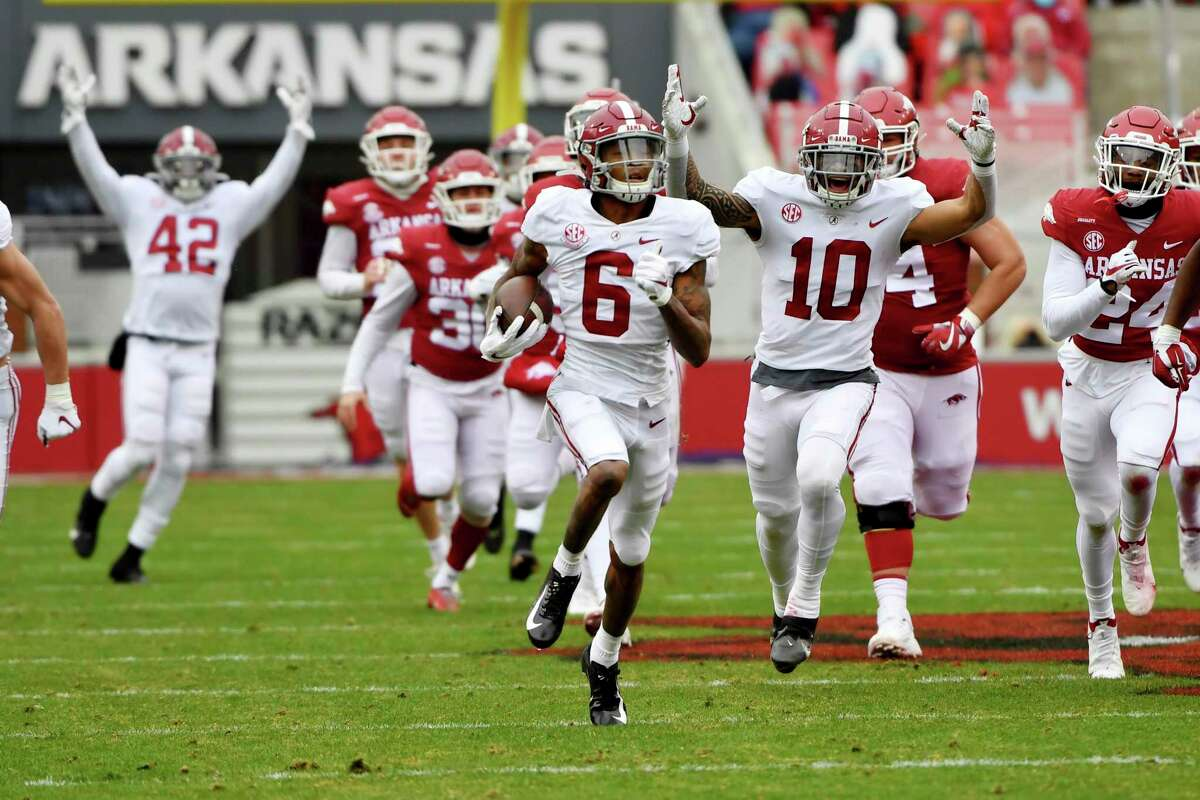 Alabama punt returner DeVonta Smith (6) returns a punt for a touchdown against Arkansas during the first half of an NCAA college football game Saturday, Dec. 12, 2020, in Fayetteville, Ark. (AP Photo/Michael Woods)
