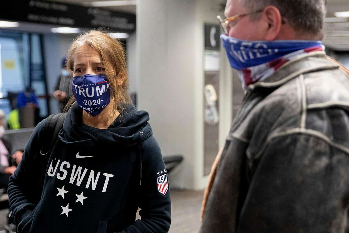 Trump supporter Doreyne Douglas (left) and Robert Douglas of Oakland wear Trump apparel while waiting for their bags at San Francisco International Airport in San Francisco, Calif. Thursday, January 7, 2021 after returning from the Stop the Steal march in Washington D.C.