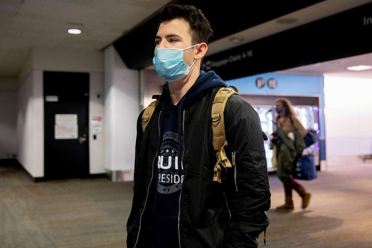 Trump supporter Jacob Burnett of Danville wears a mask and a Trump sweatshirt while arriving at San Francisco International Airport in San Francisco, Calif. Thursday, January 7, 2021 after returning from the Stop the Steal march in Washington D.C.