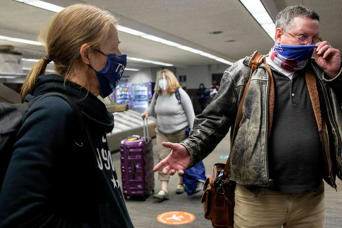 Trump supporter Doreyne Douglas and Robert Douglas of Oakland wear Trump apparel while waiting for their bags at San Francisco International Airport in San Francisco, Calif. Thursday, January 7, 2021 after returning from the Stop the Steal march in Washington D.C.