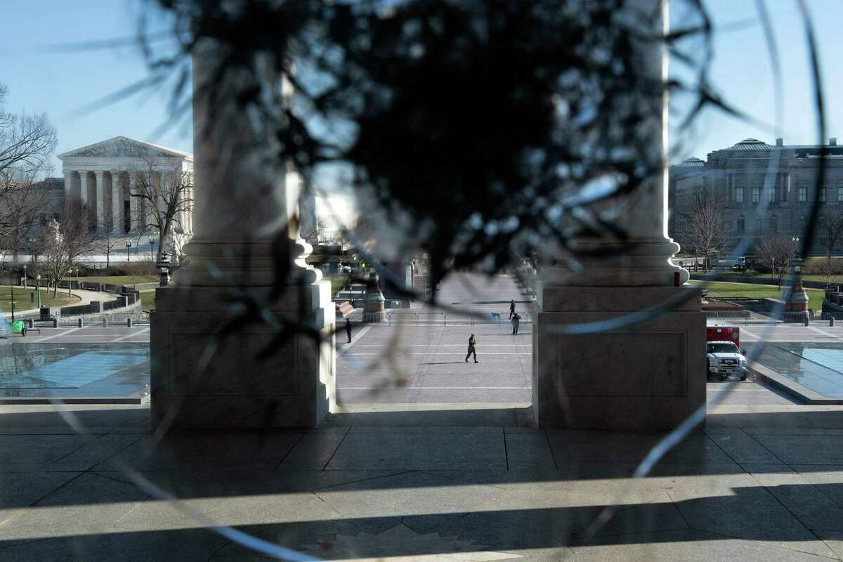 The US Supreme Court (L) is seen through a broken window a day after a pro-Trump mob broke into the US Capitol January 7, 2021, in Washington, DC. (Photo by Brendan Smialowski / AFP) (Photo by BRENDAN SMIALOWSKI/AFP via Getty Images)