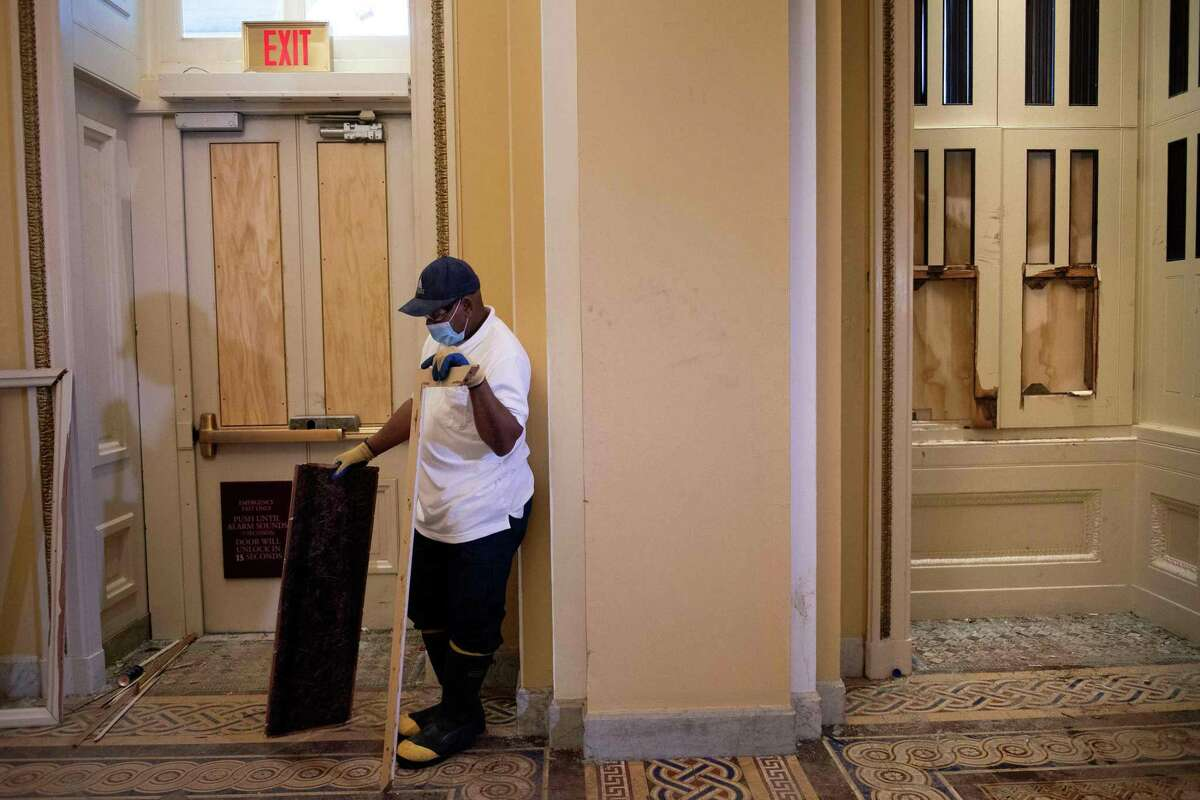 A worker pauses while clearing broken doors and windows near an entrance breached by protesters a day after a pro-Trump mob broke into the US Capitol January 7, 2021, in Washington, DC. (Photo by Brendan Smialowski / AFP) (Photo by BRENDAN SMIALOWSKI/AFP via Getty Images)