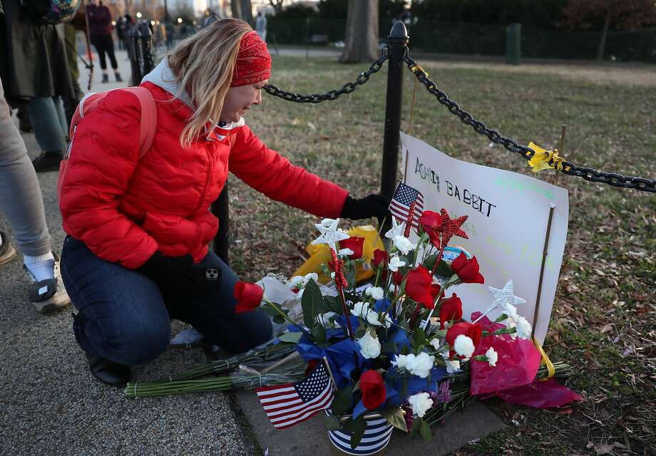 Melody Black, from Minnesota, becomes emotional as she visits a memorial set up near the U.S. Capitol building for Ashli Babbitt, who was killed in the building after the pro-Trump mob broke in. Photo: Joe Raedle, Getty Images