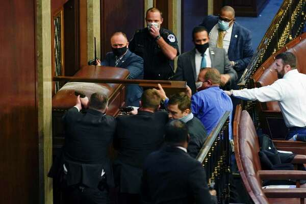 U.S. Capitol Police with guns drawn stand near a barricaded door as protesters try to break into the House Chamber at the U.S. Capitol on Wednesday, Jan. 6, 2021, in Washington. Standing nearby is sheriff-turned-congressman Troy Nehls, in a royal blue shirt.