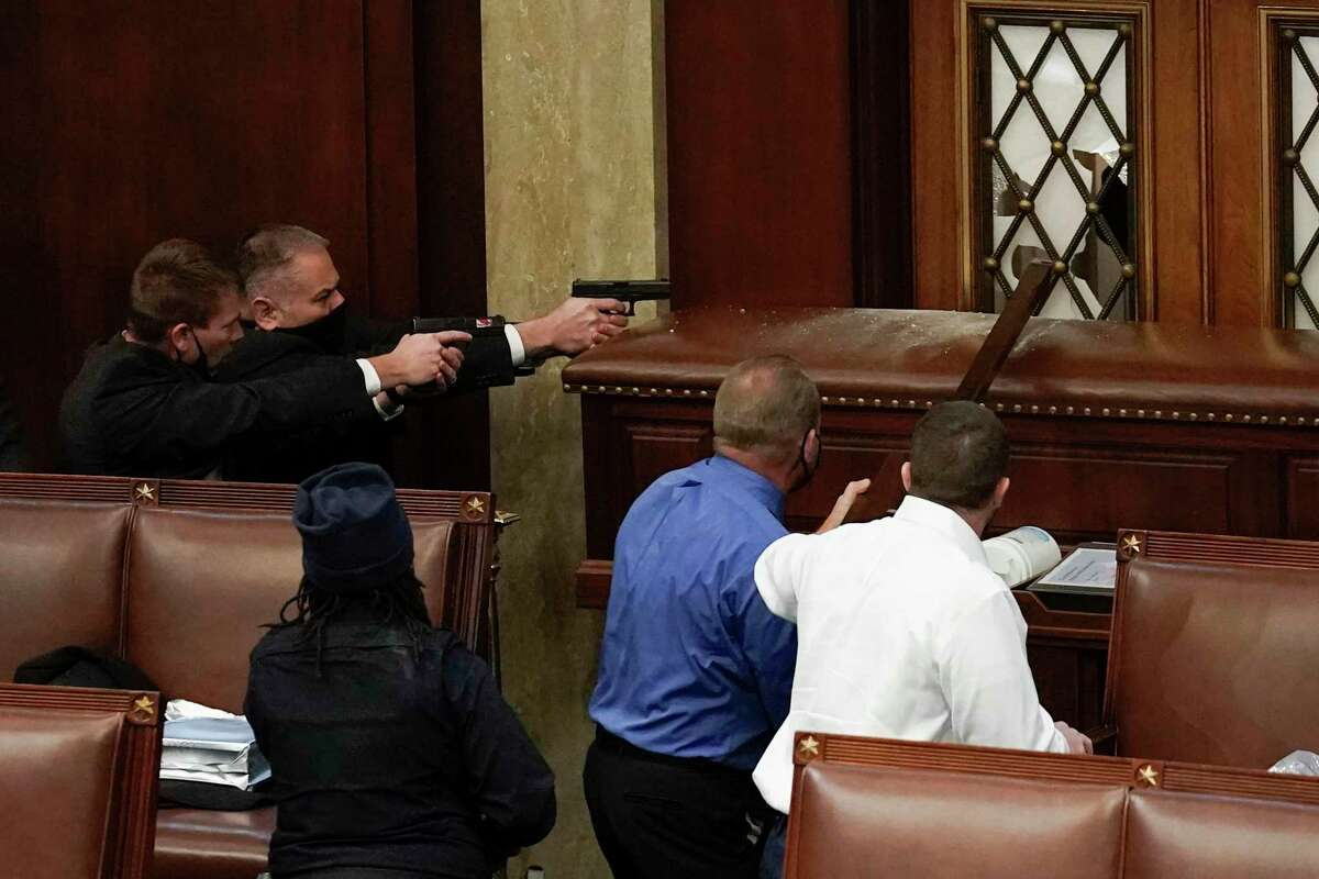 U.S. Capitol Police with guns drawn watch as protesters try to break into the House Chamber at the U.S. Capitol on Wednesday, Jan. 6, 2021, in Washington. Standing nearby is sheriff-turned-congressman Troy Nehls, in a royal blue shirt.