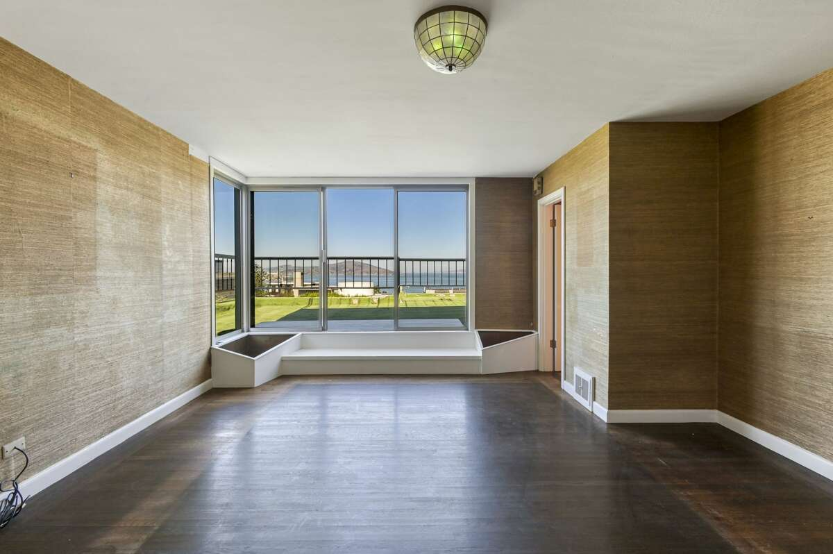 The home faces the bay, and this wall of windows steps out onto a huge artificial turf deck with a 180-degree view. Sixties features like this and the built-in that straddles the glass door and wood floor are rare creatures in today's SF real estate.