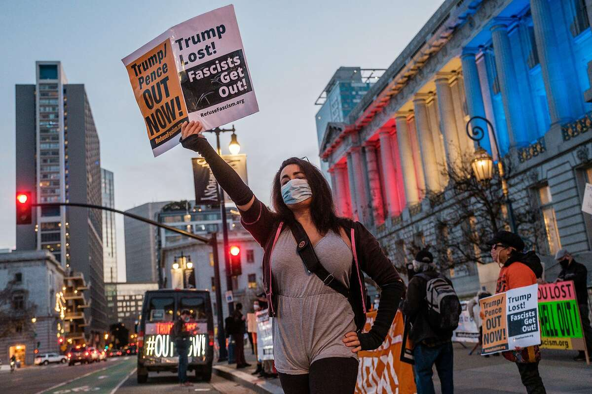 Bianca Von Krieg waves a sign at passing cars during a 'Refuse Fascism' protest in San Francisco on Thursday, January 7, 2021. A small but vocal group of people demanding Trump leave office now descended on City Hall before marching to the Twitter building.